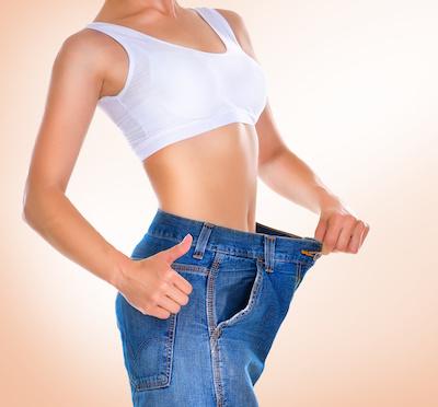 Mujer mostrando cuanto peso ha perdido con el jean bien holgado. Suplementos para bajar de peso.